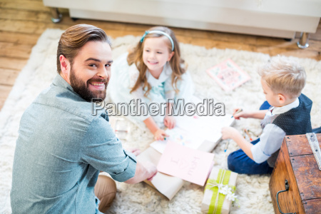 father and kids packing gifts
