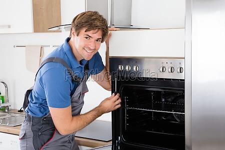 repairman with screwdriver fixing oven