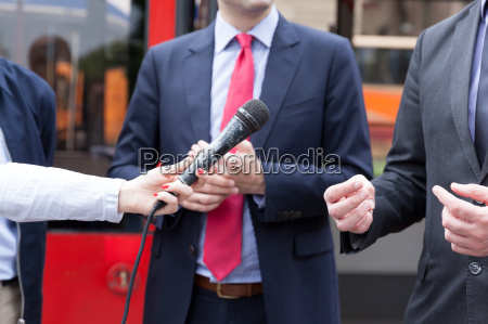 journalist holding microphone conducting media interview