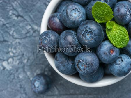 blueberries in spoon on dark background