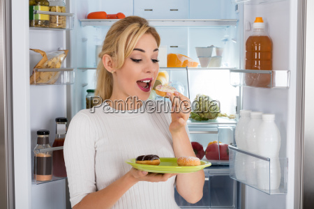 young woman eating donut from plate
