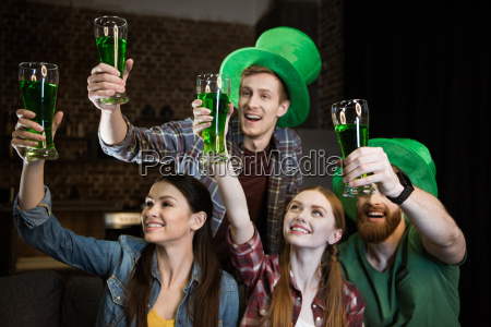 cheerful friends holding glasses with beer