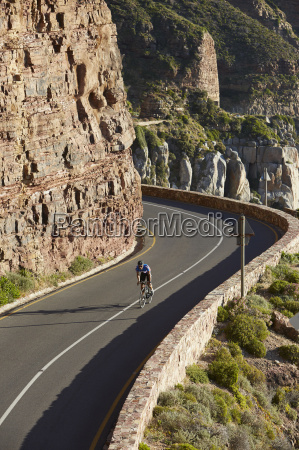 male triathlete cyclist cycling uphill along