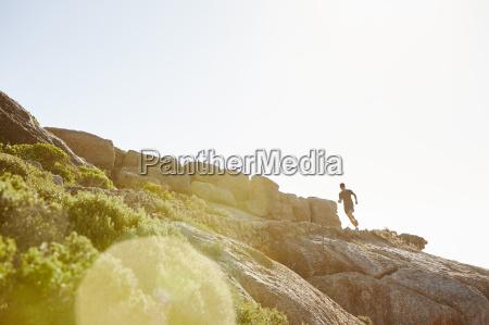 male triathlete runner running on sunny