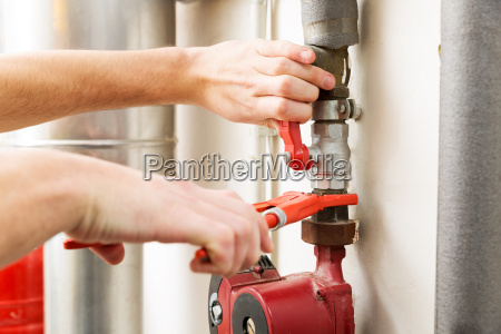 closeup of plumber hands working with