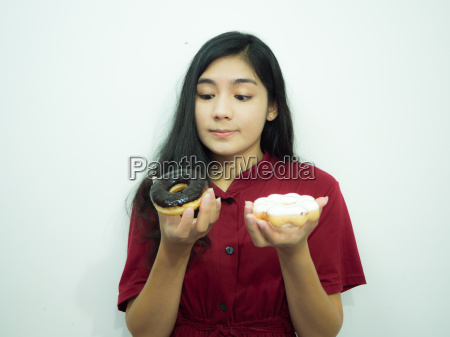 asian woman holding donut on white