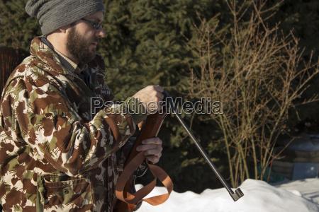 man in winter forest reloads pneumatic