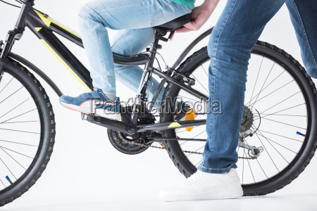 partial view of father holding bicycle
