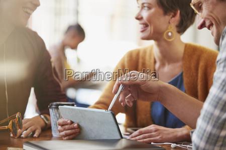 smiling business people meeting using digital