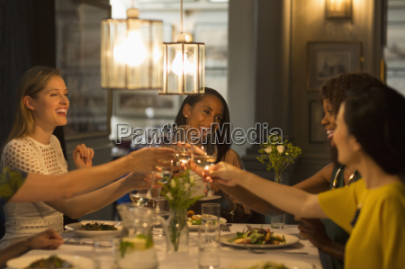 smiling women friends toasting white wine
