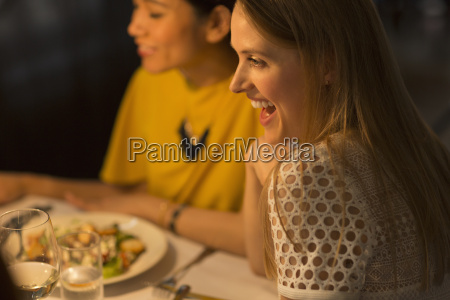 smiling woman dining with friends at