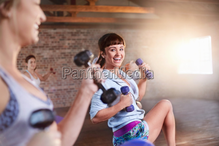 smiling young women with dumbbells in