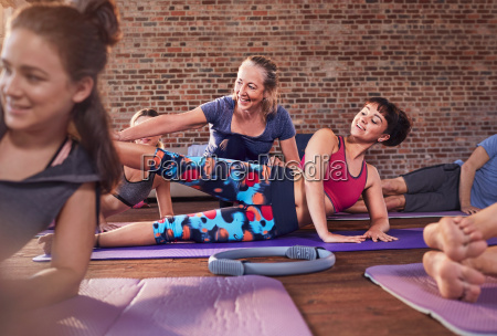 fitness instructor adjusting young woman in