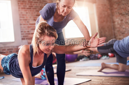 fitness instructor helping young woman practicing