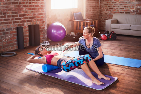 fitness instructor helping young woman doing