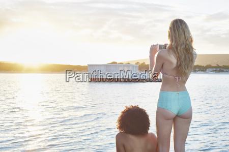 young woman in bikini photographing houseboat