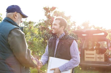male farmer and customer handshaking in