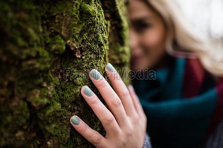 kobieta ukrywa sie za pniu drzewa