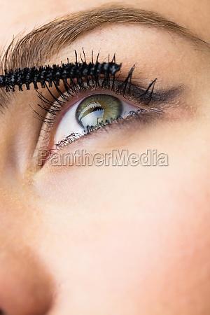 beautiful woman applying mascara on eyelashes