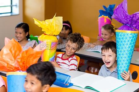 cheerful children with craft work sitting
