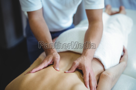 physiotherapist giving back massage to a