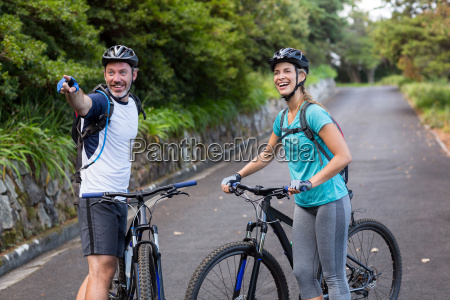 athletic couple with mountain bike pointing