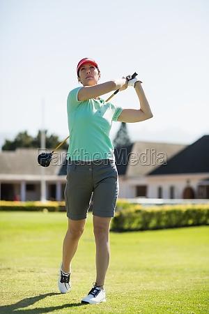 full length of golfer woman taking