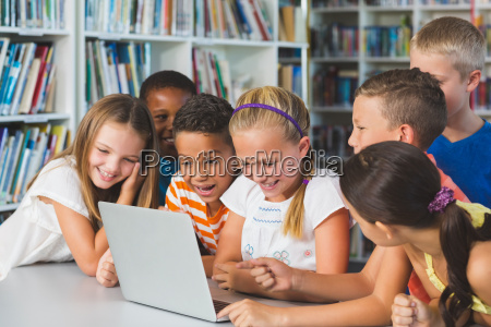 smiling school kids looking at laptop