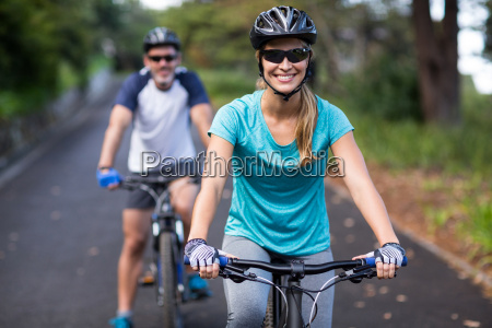 athletic couple cycling on the open