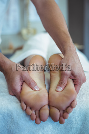 physiotherapist giving foot massage to a