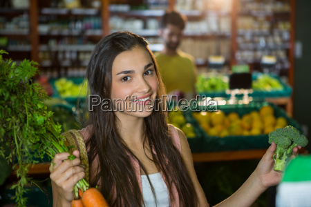woman buying carrot and broccoli in