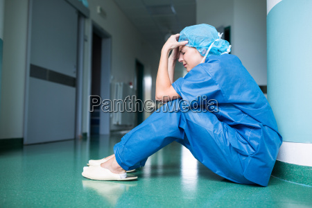 sad surgeon sitting on floor in