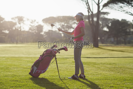 side view of woman carrying golf