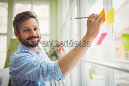 portrait of businessman writing on adhesive