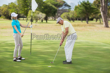 mature man and woman playing golf