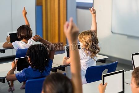 children with digital tablets raising their