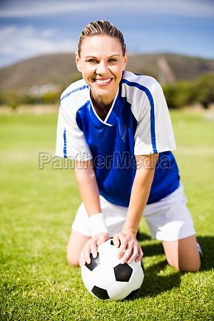 female football player kneeling on field