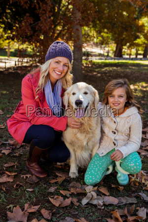 mother and daughter caressing their dog