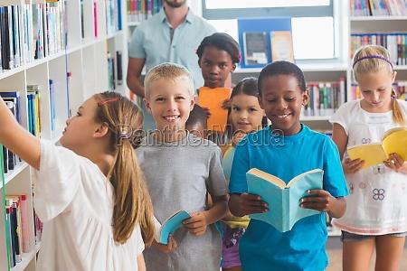 girl removing book from bookshelf in