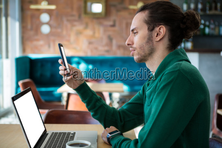 man using mobile phone with laptop