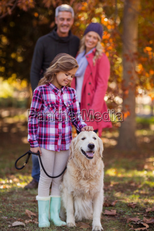 girl stroking dog while parents at