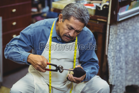 shoemaker hammering on a shoe