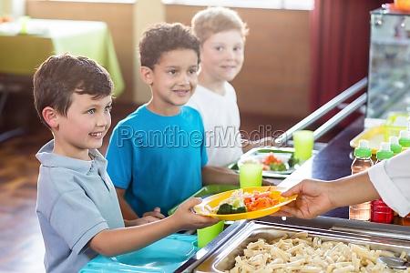 woman serving food to smiling schoolchildren