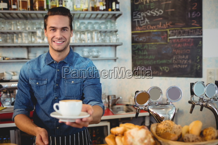 portrait of happy owner offering coffee