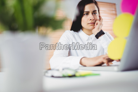 focused woman working on laptop in