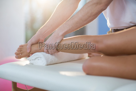male physiotherapist giving knee massage to