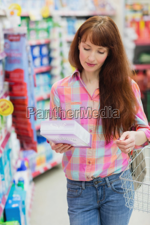 woman with shopping basket holding product