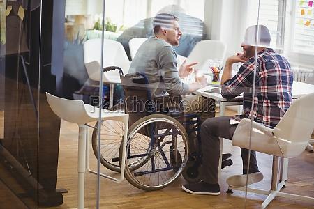 full length of handicap businessman discussing