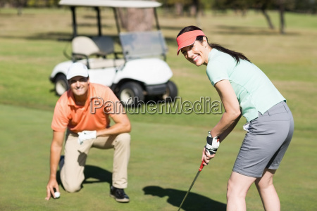 portrait of smiling woman playing golf
