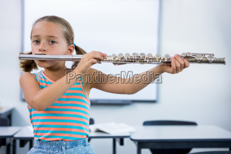 portrait of elementary girl playing flute